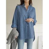 بلوزة نسائية سادة اللون بياقة مقلوبة غير منتظمة بحاشية صدر بجيوب على شكل قميص جينز منقسم